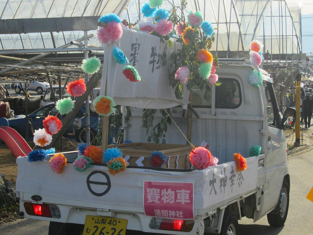 お神輿のあとには賽物車が来ます。お賽銭を入れ たら、トラックに付いている紙のお花を頂けました。